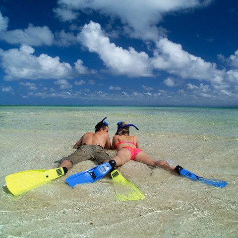 Couple Wearing Flippers Lying on Beach
